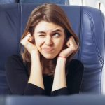 Why does chewing gum help with stuffy ears in an airplane?